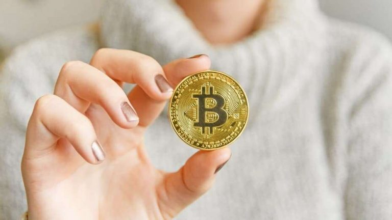 106820278 1609972654383 hand holding a bitcoin in front of a computer screen with a dark graph blockchain mining bitcoin t20 prrrjp